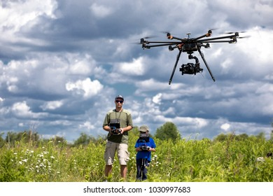 father and son  playing with RC quadrocopter , dron