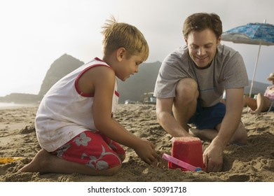 Father and Son Playing in Sand at Beach