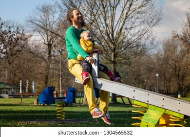 Father and son playing at seesaw in public playground, Zagreb, Croatia.