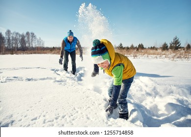 father and son playing with snow in the winter outdoors