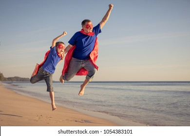 Father and son playing superhero on the beach at the day time. People having fun outdoors. Concept of summer vacation and friendly family.