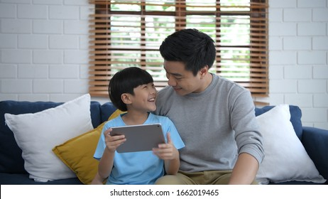 Father and son are playing tablets in the living room.