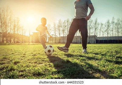 Father and son playing together with ball in football under sun light. Green field in city park at sunny day.