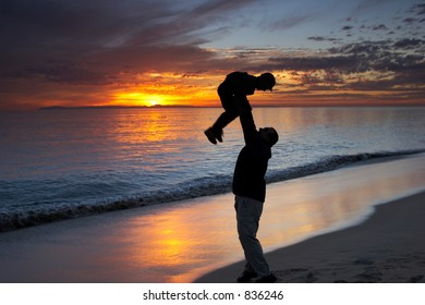 Father and son playing together on a beach at sunset