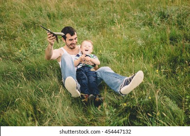father and son playing with a toy airplane in a field