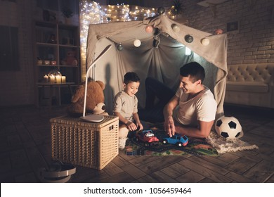Father and son are playing with toy cars on carpet road in blanket fort at night at home.