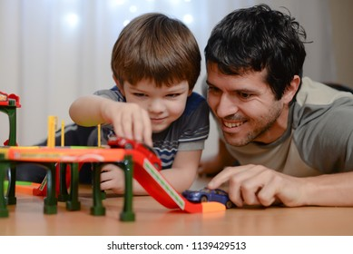 Father and son are playing with toy cars. Happy family playing with toys