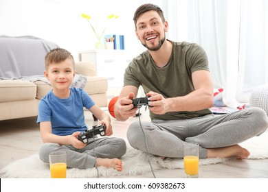 Father and son playing videogame at home