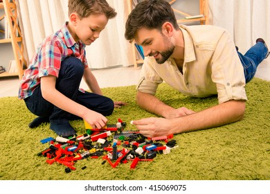 Father and son playing with constructor while lying on carpet