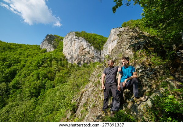 Father and son posing on the high mountains in a sunny spring day
