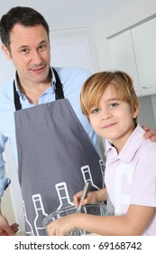 Father and son preparing cake in kitchen