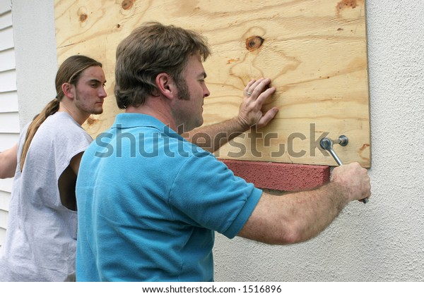 A father & son preparing for a hurricane by putting plywood over the windows.