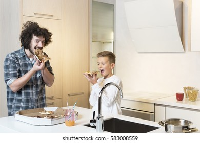 father and son preparing lunch and eating pizza together at home in the kitchen