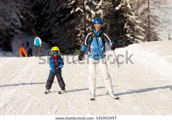 Father and son, preschool child, skiing in austrian ski resort in the mountains, wintertime