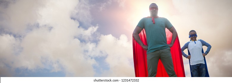 Father and son pretending to be superhero against blue sky with white clouds