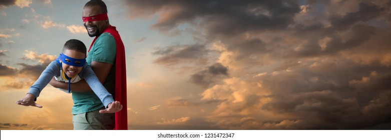 Father and son pretending to be superhero against blue and orange sky with clouds