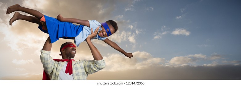Father and son pretending to be superhero against cloudy sky landscape