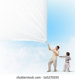 father and son pulling blank banner. Place for text