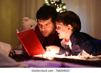 Father and son reading book for Christmas eve. Dad reading a fairytale to his son under a christmas tree