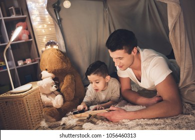Father and son are reading book with magnifying glass in blanket fort at night at home.