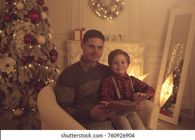Father and son reading book near Christmas tree at home.