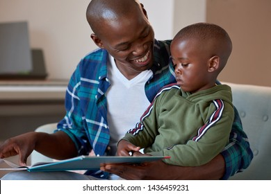 Father and son reading a book on the couch, loving family time at home