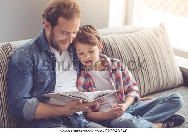 Vater und Sohn lesen ein Buch und lächeln, während sie zu Hause Zeit zusammen verbringen