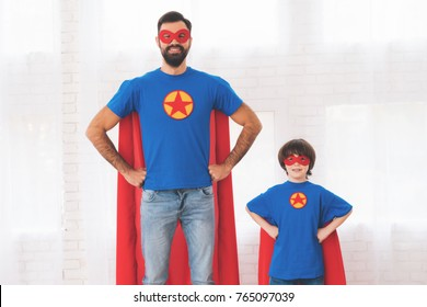 Father and son in the red and blue suits of superheroes. On their faces are masks and they are in raincoats. They are posing in a bright room.
