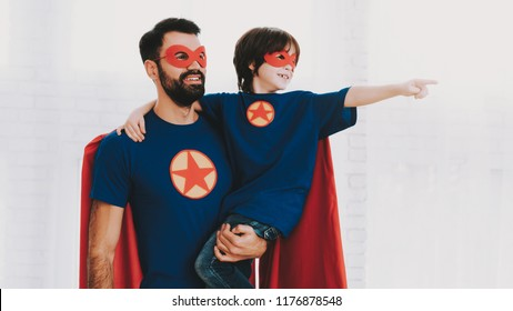 Father And Son. Red And Blue Superhero Suits. Masks And Raincoats. Posing In A Bright Room. Young Happy Family Holiday Concept. Resting Together. Save The World. Get Ready. Strong And Powerful.