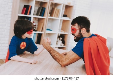 Father And Son. Red And Blue Superhero Suits. Arm Wresling Competition. Masks And Raincoats. Bright Room. Young Happy Family Holiday Concept. Resting Together. Strong And Powerful.