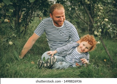father and son with red hair are resting in the garden under an apple tree