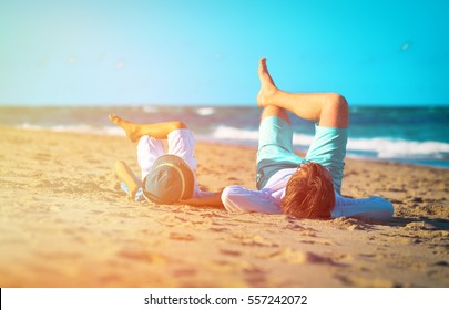 father and son relax on the beach