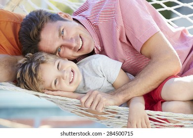 Father And Son Relaxing In Garden Hammock Together