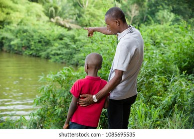 Father and son relaxing together in the forest, young father shows the importance of the river and the forest to his son