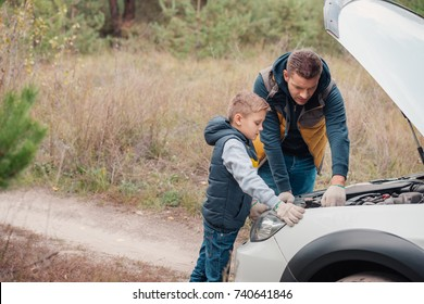 father and son repairing car engine together in forest