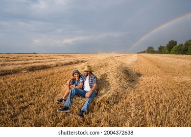Father and son are resting after successful harvest. Rainbow in the sky behind them.