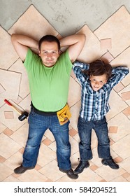 Father and son resting on unfinished floor tiles surface - resting after work