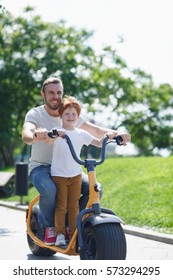 Father and son resting together. Full length photo of young happy dad with cute little boy  riding electric scooter in summer park outdoors