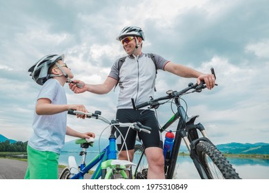 Father and son ride, cycling their bikes together, on sunny day, Happy family in helmets is riding bikes having fun.