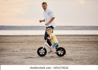 Father with son riding bicycle in summer. Man runs along with kid on the beach at sunset. Son learns to ride a bike