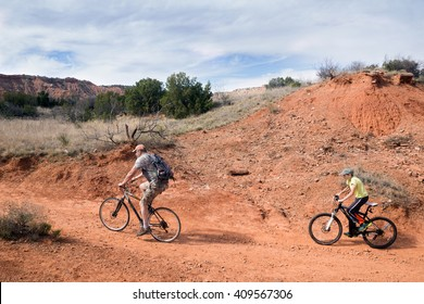 Father and son riding bikes on the trail. Palo Duro Canyon State Park, Texas, US