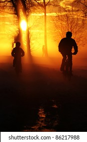 Father and son riding through misty sunset