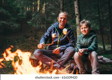 Father and son roast marshmallow candies on the campfire in forest. Spring or autumn camping