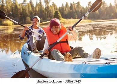 Father And Son Rowing Kayak On Lake