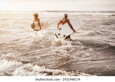 Father and son running on the beach at sunset for surf training - Focus on right man