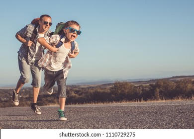 Father and son running on the road at the day time. Concept of tourism.