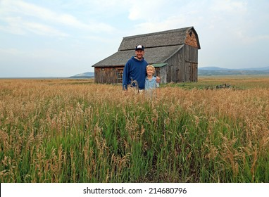 Father and son in a rural field with a rustic barn, Wyoming, USA.