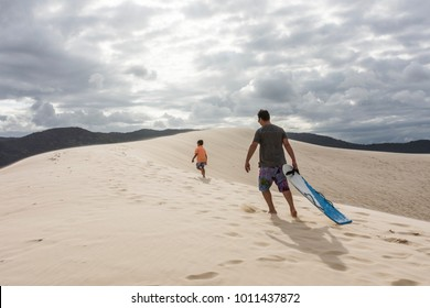 Father and son sandboarding on sand dunes in Joaquina Beach, Florianopolis, Santa Catarina Island, South Brazil