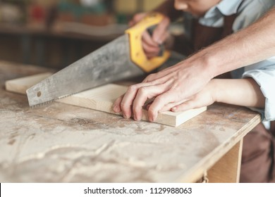 Father and son sawing a board in the carpentry