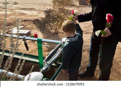 A father and son say goodbye to a loved one by throwing roses into an open grave during a burial at relatively new, dusty cemetary in the desert.